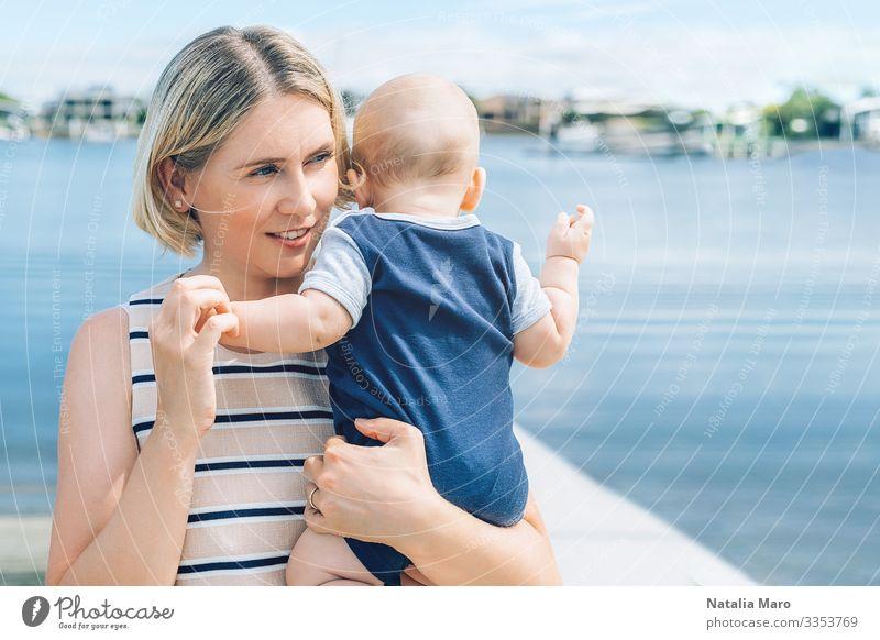 Mutter hält einen kleinen Sohn mit einer Meeresbucht im Hintergrund Freude Glück schön Gesicht Leben Sommer Strand Kindererziehung Baby Kleinkind Frau