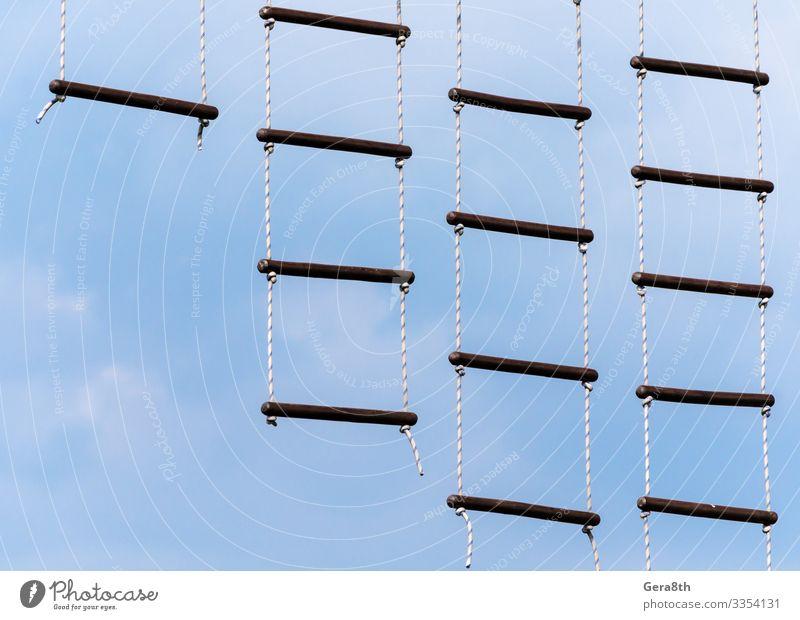 Strickleiter gegen blauen Himmel und Wolken Klettern Bergsteigen Seil Kugel Farbe abstrakter Hintergrund Querbalken empyreisch Äther Fußweg aufstehen