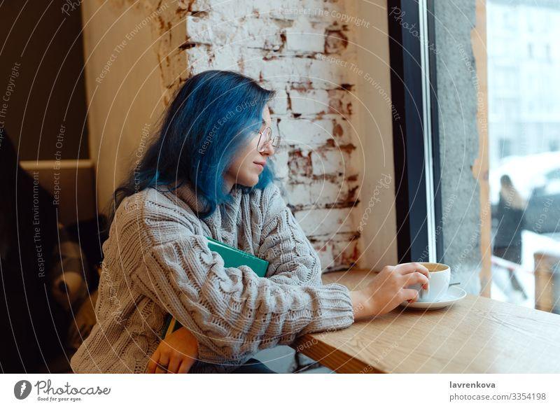 Junge erwachsene Frau mit blau gefärbten Haaren trinkt Kaffee in einem Coffeeshop während der Blauen Stunde, flacher selektiver Fokus Asiate gemütlich Abend
