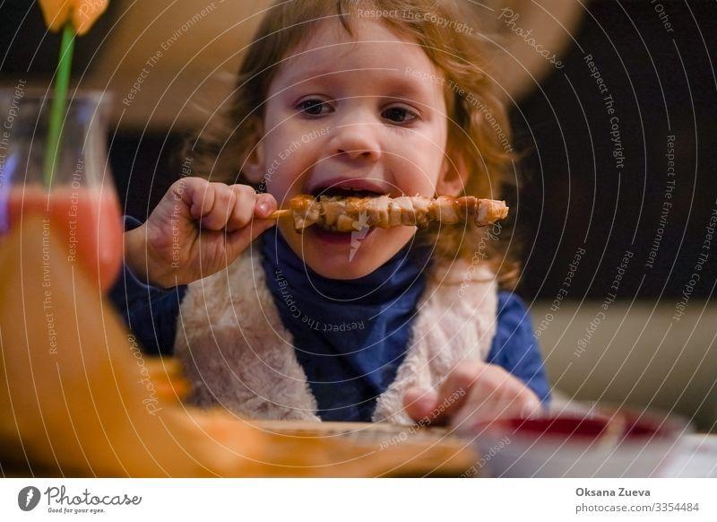 Das kleine blonde Mädchen isst gerne Kebab. Zeit für das Abendessen. Blick in die Kamera Innenaufnahme Speise Essenszeit Genuss geschmackvoll Mahlzeit