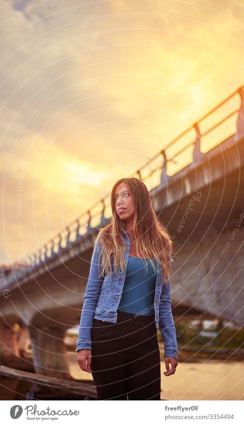Porträt einer jungen Frau vor einer Stadtbrücke Lächeln Jeansstoff Jacke blau Sommer urban Brücke Zement blond Mädchen glühen Sonnenlicht Großstadt Gebäude Tag