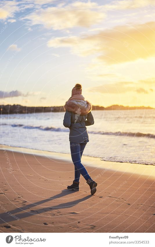 Junge Frau geht bei Sonnenuntergang in Vigo mit Winterkleidung am Strand spazieren jung rückwärts Bekleidung laufen Urlaub Menschen Sand MEER Herbst fallen