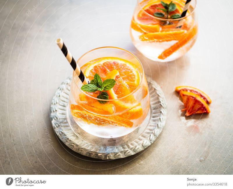 Cocktail mit frischen Orangen und Pfefferminze in einem Glas Kräuter & Gewürze Minze Diät Getränk Trinkwasser Limonade Saft Longdrink Teller Trinkhalm Lifestyle