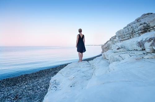 Ein einsames Mädchen in einem schwarzen Kleid am Meeresufer. Weiße Steine. schön Frau Erwachsene 18-30 Jahre Jugendliche Natur Landschaft Sommer Schönes Wetter