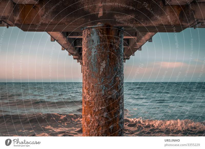 rostige Seebrücke von unten Himmel Sommer Schönes Wetter Wellen Ostsee Meer Rost Unendlichkeit maritim blau braun rosa ruhig Fernweh Symmetrie Brücke symetrisch