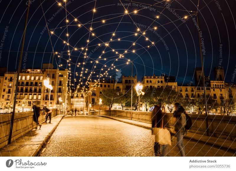 Menschen gehen abends auf einer beleuchteten Brücke in der Stadt laufen Illumination Großstadt Lehnen urban Architektur Abend Gebäude Nacht Dämmerung