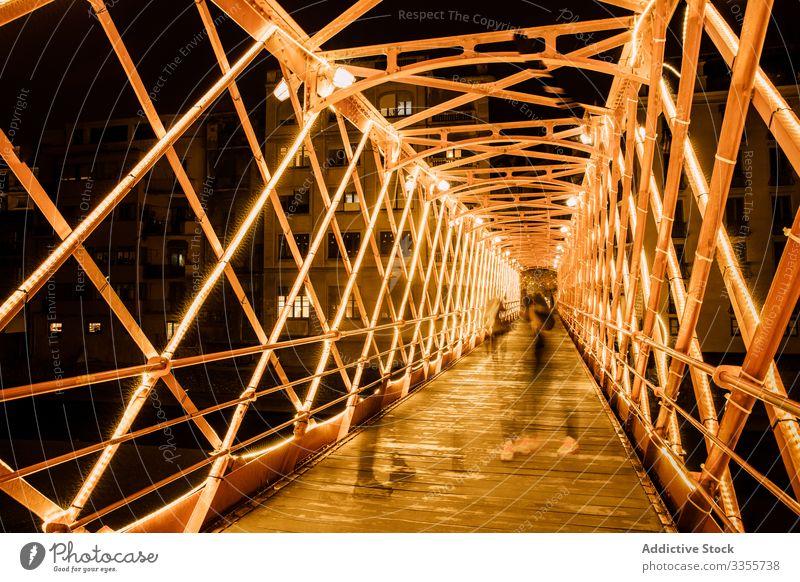 Menschen gehen abends auf beleuchteter Brückenkonstruktion Konstruktion laufen Illumination Großstadt Lehnen urban Architektur Abend Gebäude Nacht Dämmerung