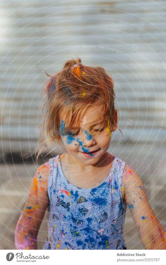 Schmutziges Mädchen auf der Straße mit Farbe bedeckt Stadtfest nehmen fokussiert dreckig wenig Sommer Wochenende Kind unordentlich Feiertag konzentriert