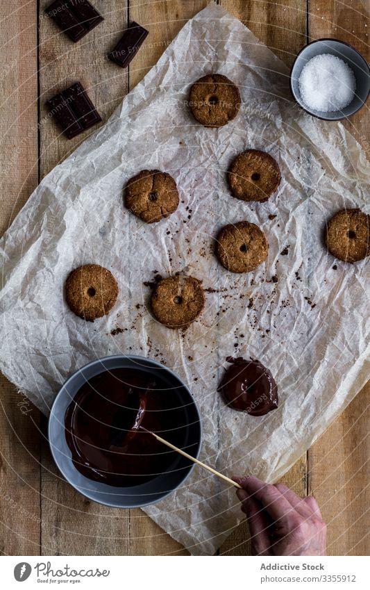 Cook gießt gebackene Kekse mit Schokoladensirup auf Backpapier Koch Gießen Sirup Bäckerei Lebensmittel selbstgemacht Essen zubereiten Vorbereitung Kuchen Küche