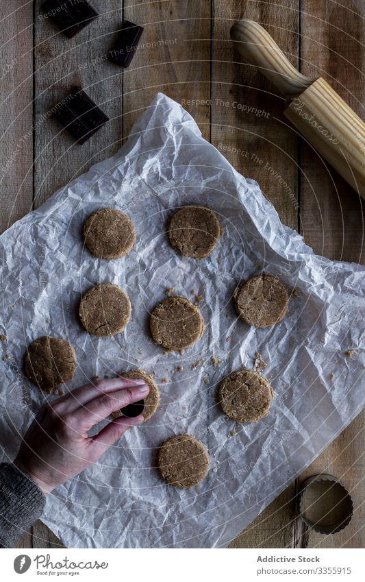 Koch hält Schokoladenteig in der Hand auf Backpapier Teigwaren Mehl Nudelholz Kochform Metall Bäckerei Lebensmittel selbstgemacht Essen zubereiten Vorbereitung