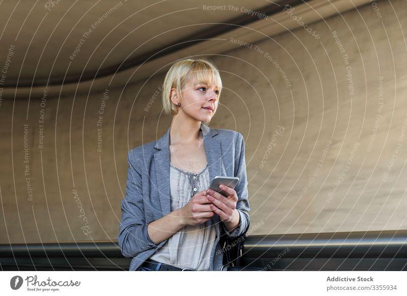 Lächelnde Geschäftsfrau mit Smartphone stylisch jung heiter Geländer Lehnen Frau professionell Person schön benutzend Browsen attraktiv Unternehmer elegant