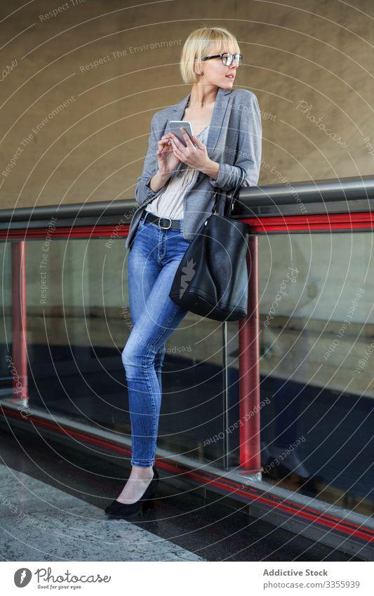 Geschäftsfrau mit Smartphone stylisch jung Telefon Mobile Anschluss heiter Geländer Lehnen Frau professionell Person schön benutzend Browsen attraktiv
