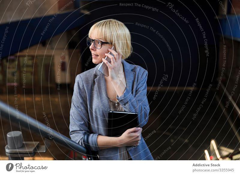 Blonde Geschäftsfrau spricht auf Smartphone stylisch jung Frau Notizblock Telefon Mobile Anschluss sprechend Mitteilung Gespräch professionell Person schön