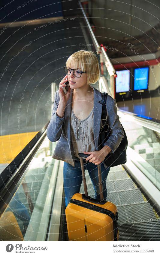 Geschäftsfrau mit Gepäck telefoniert stylisch jung Smartphone Rolltreppe Frau professionell Person schön Ausflug reisen Station Flughafen Terminal Gespräch