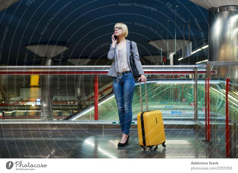 Geschäftsfrau mit Gepäck telefoniert stylisch jung Smartphone Telefon Mobile Anschluss Frau professionell Person schön Ausflug reisen Station Flughafen Terminal