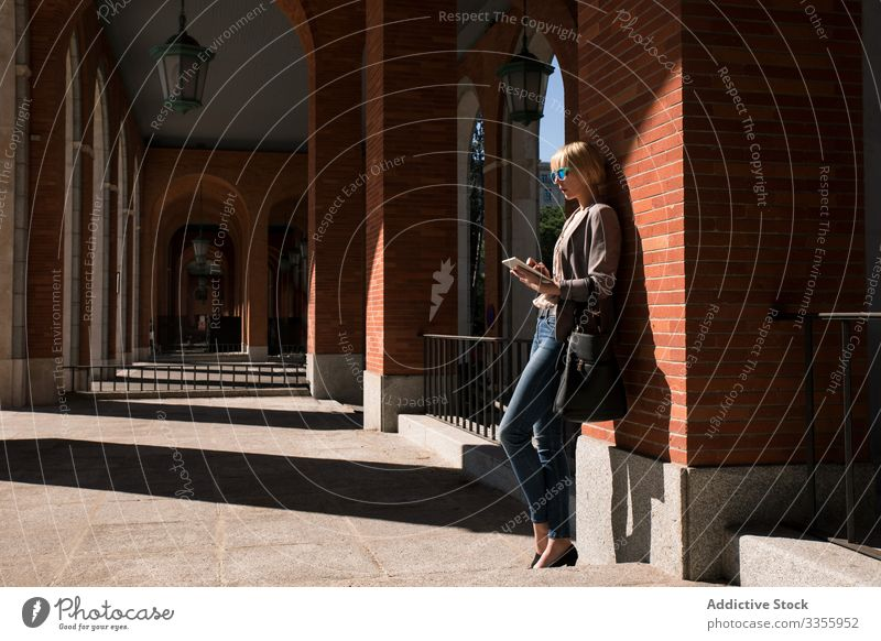 Geschäftsfrau mit Tablette an der Wand stylisch jung Frau Browsen zuschauend Lehnen Backsteinwand professionell Person schön attraktiv Sonnenbrille Wegsehen