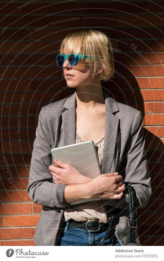 Geschäftsfrau mit Tablette an der Wand stylisch jung Frau Lehnen Backsteinwand professionell Person schön attraktiv Sonnenbrille Wegsehen Unternehmer elegant