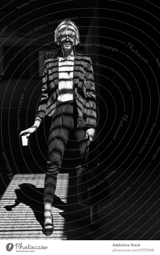 Modische Frau mit Pappbecher Geschäftsfrau stylisch jung Fenster Fensterläden Schatten Papier Tasse in die Kamera schauen Stehen Linien streifen professionell