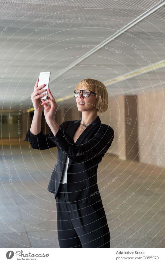Geschäftsfrau benutzt Smartphone im Flur stylisch jung Frau Stehen Saal Selfie benutzend Browsen unter professionell Person schön attraktiv Unternehmer elegant