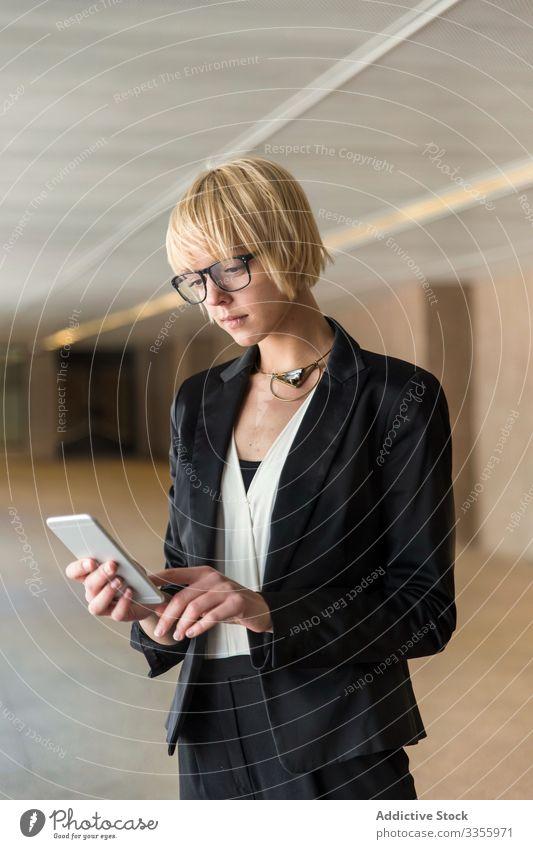 Stilvolle Geschäftsfrau surft auf Smartphone Telefon Mobile Anschluss Browsen zuschauend stylisch jung Frau selbstbewusst Saal professionell Person schön