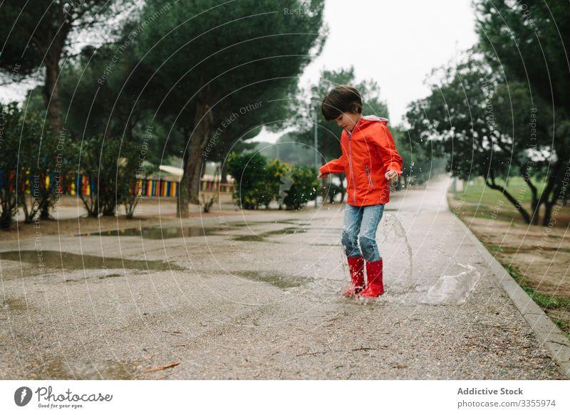Aktives Kind springt in Pfütze in Parkallee springend unordentlich Saison lustig Wasser nass Schmutz Kindheit Wetter Schlamm Herbst Spiel aktiv Gummistiefel