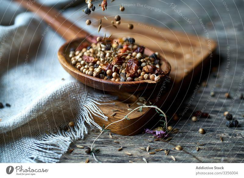 Trockene Mischung aus Gewürzen und getrockneten Beeren in einem Löffel auf dem Tisch duftig Kraut Ernte reif natürlich Paprika Gesundheit essbar hölzern Sammeln