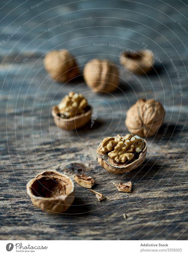 Reife, halbgeschälte Walnüsse am Holztisch Walnussholz reif Gesundheit essbar hölzern Filbert Ernte Sammeln Nut Haufen Bestandteil natürlich organisch roh
