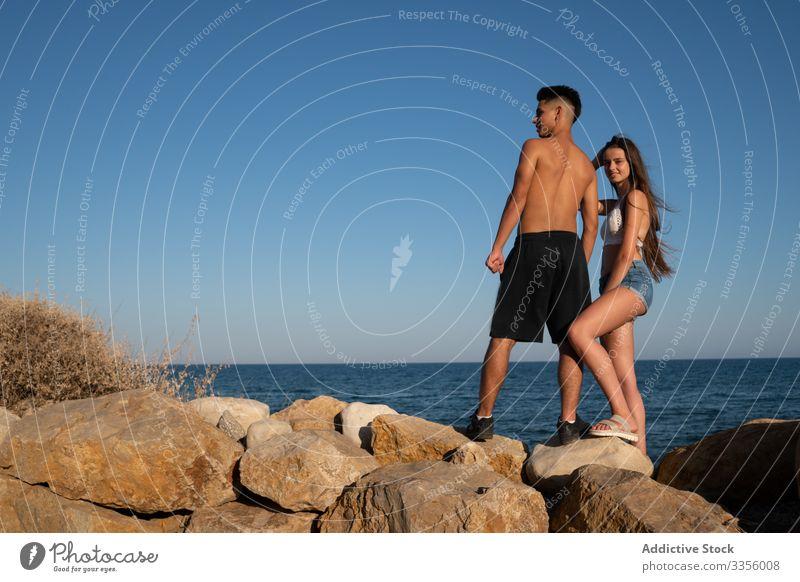 Ethnischer Mann und glückliche Frau stehen auf Stein Freund Urlaub MEER Strand reisen Glück Tourist sich[Akk] entspannen Meer Zusammensein Freizeit Aktivität