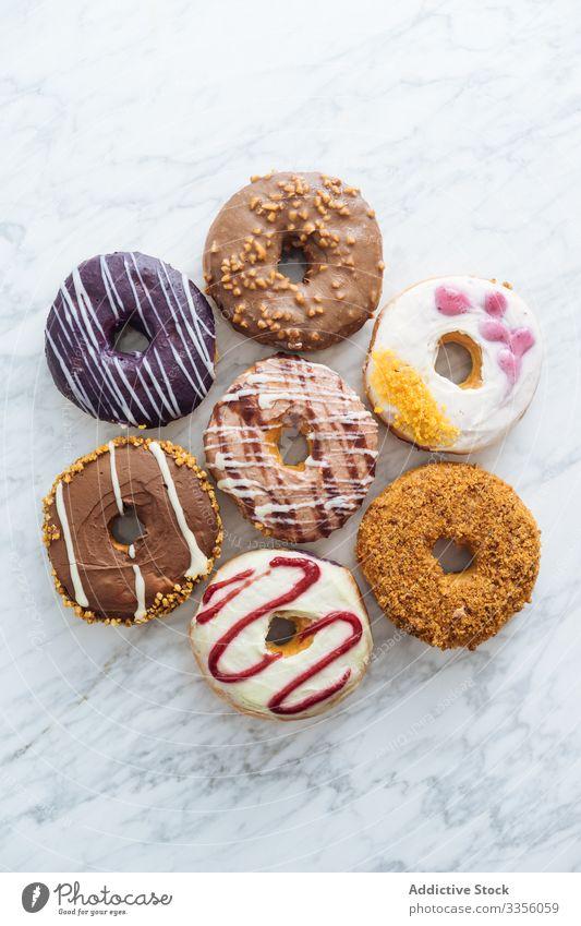 Verschiedene Doughnuts auf Marmor-Hintergrund Varieté Sortiment süß Zuckerguß verglast Lebensmittel Krapfen Bäckerei Gebäck bestäuben gebraten farbenfroh viele