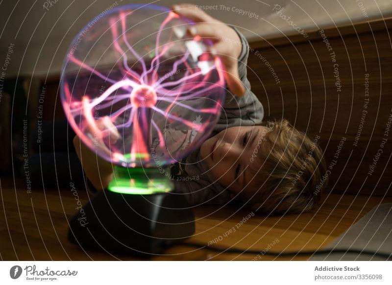 Junge betrachtet geheimnisvolle Glas-Beleuchtungslampe auf dem Tisch Blick Lampe neonfarbig elektrisch Licht leuchtend strömen Ball beleuchtet Elektrizität