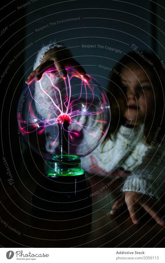 Charmantes Mädchen berührt glühende Kugel mit der Hand im Dunkeln elektrisch Licht leuchtend Lampe strömen Ball beleuchtet Elektrizität Energie Knolle hell Kind