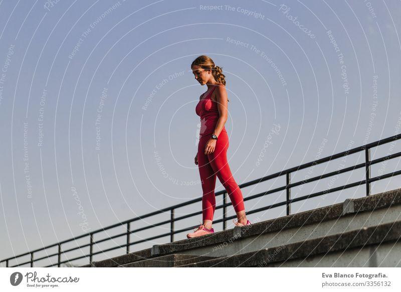 Fitness-Frau im Stadion, die bereit ist, Sport zu treiben. Tragen von roter Sportkleidung. Konzept für eine gesunde Lebensweise. Sonnenuntergang im Sommer