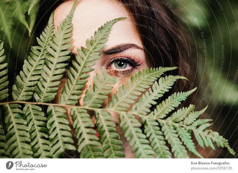 Nahaufnahme eines Porträts einer jungen schönen Frau inmitten grüner Farnblätter Sauberkeit Jugendliche attraktiv Erwachsene Hautpflege Vorderseite Gesicht
