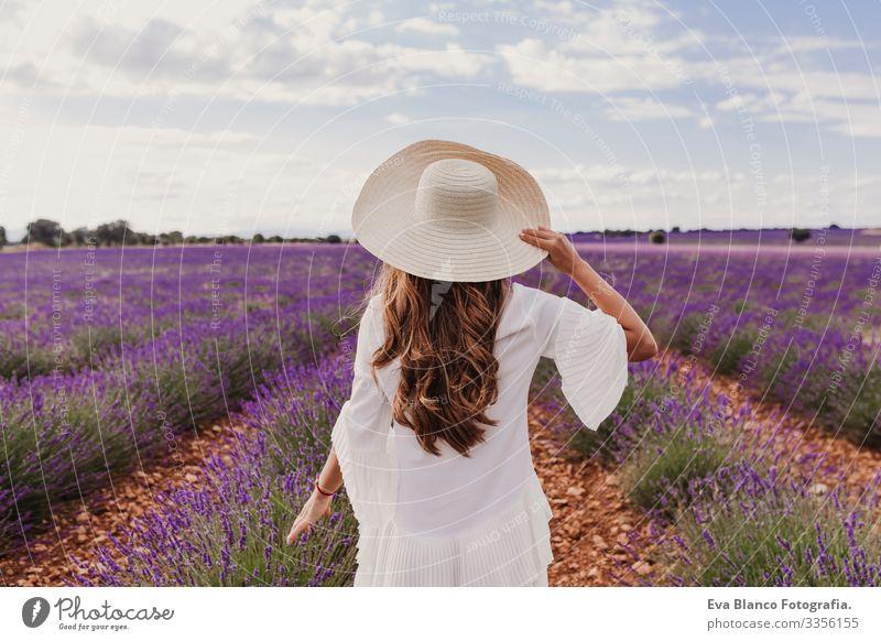 Charmante junge Frau mit Hut und weißem Kleid in einem lila Lavendelfeld bei Sonnenuntergang. LIfestyle im Freien. Rückansicht Wiese Beautyfotografie Freude