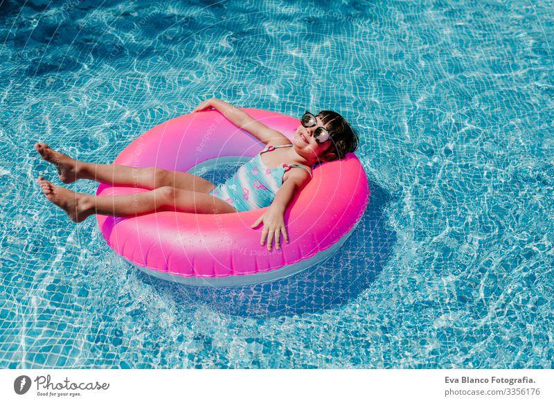 Hübsches Mädchen, das auf rosa Donuts in einem Pool schwimmt. Sonnenbrille tragen und lächeln. Spaß und sommerlicher Lebensstil Aktion Schwimmbad