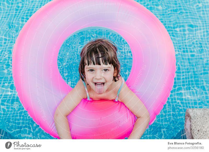 Hübsches Mädchen, das auf rosa Donuts in einem Pool schwimmt. Lächelnd. Spaß und sommerlicher Lebensstil Aktion Schwimmbad Beautyfotografie Außenaufnahme