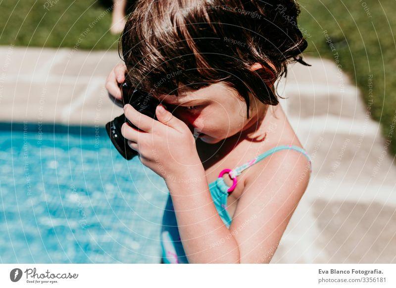 Hübsches Mädchen, das mit einer alten Oldtimer-Kamera in einem Pool fotografiert. Lächelnd. Spaß und sommerlicher Lebensstil Aktion Schwimmbad Beautyfotografie
