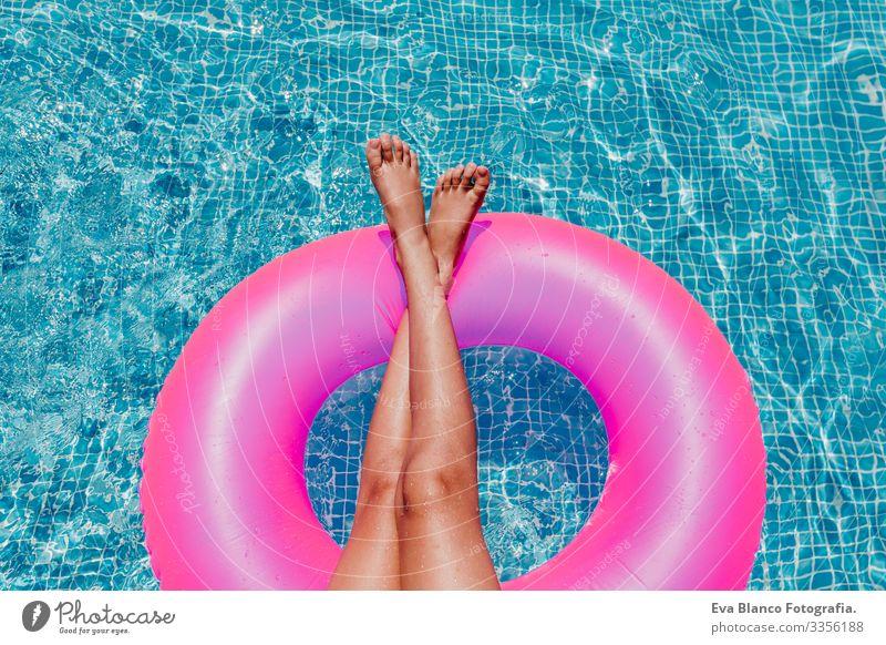 nicht wiedererkennbare Teenagerin, die auf rosa Donuts in einem Pool schwimmt. Sonnenbrille tragen und lächeln. Spaß und sommerlicher Lebensstil Aktion
