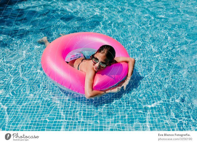 Ein wunderschöner Teenager schwimmt auf rosa Donuts in einem Pool. Sonnenbrille tragen und lächeln. Spaß und sommerlicher Lebensstil Aktion Schwimmbad