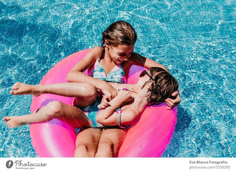 zwei wunderschöne Schwestern, die auf rosa Donuts in einem Pool schwimmen. Kitzeln und Lächeln spielen. Spaß und sommerlicher Lebensstil Aktion Schwimmbad