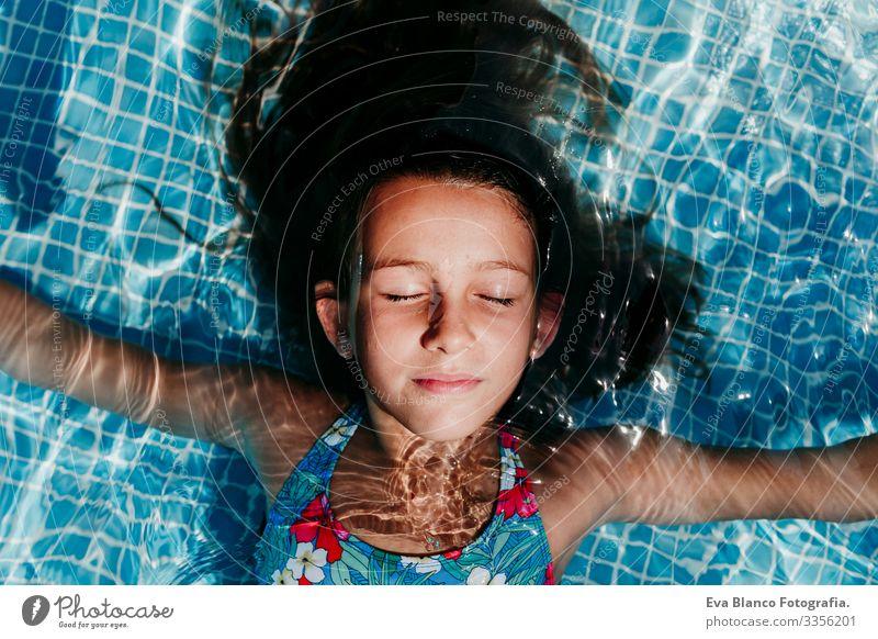 Ein wunderschöner Teenager schwebt in einem Pool und schaut in die Kamera. Spaß und sommerlicher Lebensstil Aktion Schwimmbad Beautyfotografie Außenaufnahme
