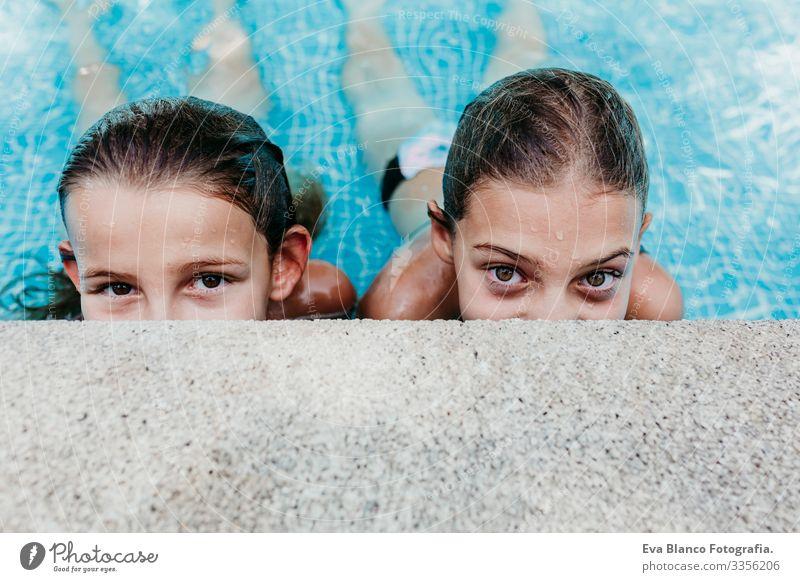 zwei wunderschöne Teenager-Mädchen, die in einem Pool schweben und in die Kamera schauen. Spaß und sommerlicher Lebensstil Aktion Schwimmbad Außenaufnahme