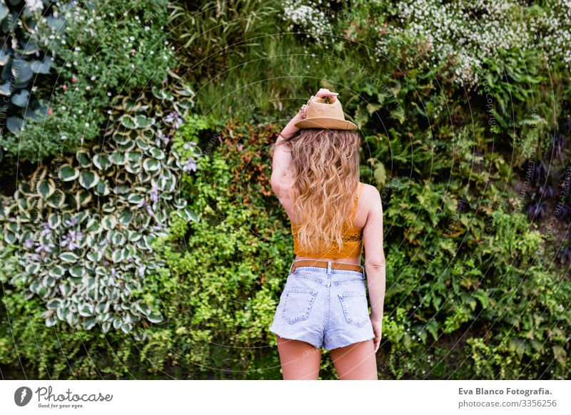 Porträt einer jungen, blonden, schönen Frau auf der Straße, die lächelt. Grüner Vegetationshintergrund. Lebensstil im Freien. Sommerzeit modern trendy Erotik