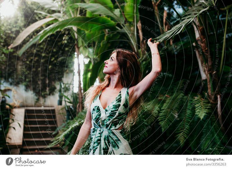 Porträt einer schönen blonden jungen Frau, die bei Sonnenuntergang in einem von tropischen Pflanzen umgebenen Gewächshaus lächelt. Glück und Lebensstilkonzept