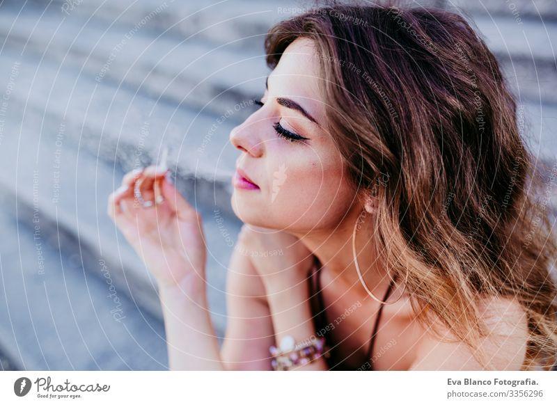 Hübsche junge kaukasische Frau, die an einem sonnigen Tag auf einer Treppe an der Straße der Stadt sitzt und eine Zigarette raucht. Urbaner Lebensstil und Raucherkonzept. Nahaufnahme