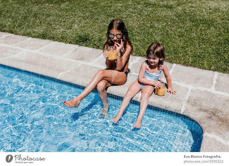 zwei schöne Schwestern am Pool, die Orangensaft trinken, Sommerzeit Kind Familie & Verwandtschaft zwei Schwestern Freundschaft Zusammensein genießen fliegend