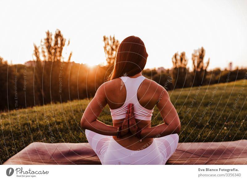 junge schöne asiatische Frau, die bei Sonnenuntergang in einem Park Yoga macht. Konzept für Yoga und gesunde Lebensweise. Rückansicht Jugendliche Sommer Glück