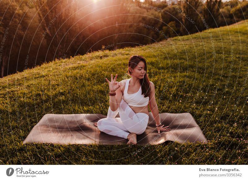 junge schöne asiatische Frau, die bei Sonnenuntergang in einem Park Yoga macht. Konzept für Yoga und gesunde Lebensweise Jugendliche Sommer Glück Genuss Sport