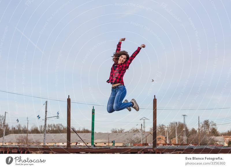 junge schöne Frau, die springt und sich glücklich fühlt. Sie trägt lockere Kleidung. Hintergrund der Stadt im Freien. Lebensstil Hut stehen attraktiv Mobile