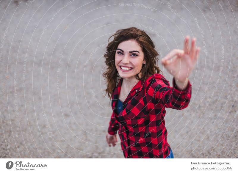 Draufsicht auf das Porträt einer jungen schönen Frau, die ein Mobiltelefon benutzt. Sie trägt lockere Kleidung und macht mit den Händen ein Ok-Zeichen. Hintergrund der Stadt im Freien. Lebensstil